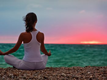 אשה עושה יוגה בתנוחת לוטוס מול הים בשקיעה